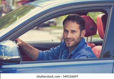 Happy man with hands on wheel driving new car