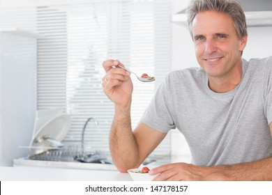 Happy man having cereal for breakfast in kitchen at home smiling at camera