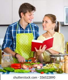 Happy man helping young wife to prepare healthy dinner