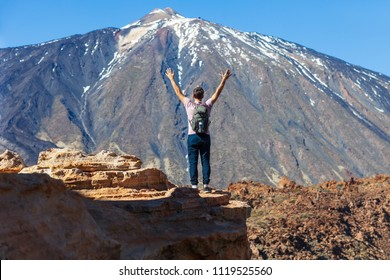Happy man hiker with backpack standing on the edge of rock with raised hands enjoying volcano El Teide in National park of Tenerife, Canary Islands, Spain. Travel concept. Back view portrait
