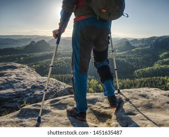 Happy man hiker hold medicine stick,  injured knee fixed in knee brace feature. Scenic mountain top with deep misty valley bellow