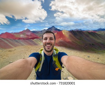 happy man hiker takes photo selfie in Vinicunca, Peru with background of Rainbow Mountain (5200 m) in Andes, Cordillera de los Andes, Cusco region in South America with cloudy sky