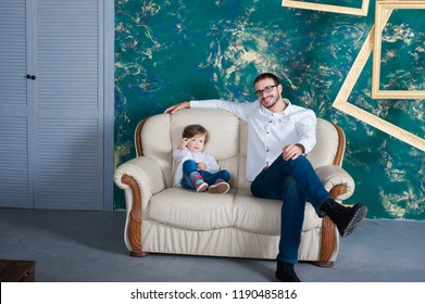 happy man and his arms embrace his son. Family mod on the sofa at home. White shirt. Father's Day