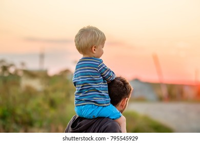 Happy man and his child having fun outdoors. Family lifestyle rural scene of father and son in sunset sunlight.