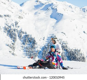 Happy man and his daughter sitting on top of Alps, resting after skiing against wonderful winter mountains background