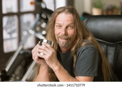 Happy man at his desk with a coffee and motorcycle in the background