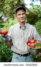 Happy man in his urban garden holding just picked ripe tomatoes.