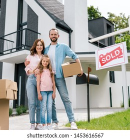 happy man holding box and standing with family near house and board with sold letters