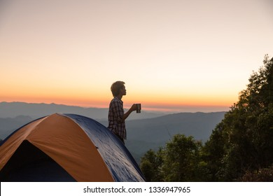 Happy man with holding coffee cup stay near tent around mountains under sunset light sky enjoying the leisure and freedom.