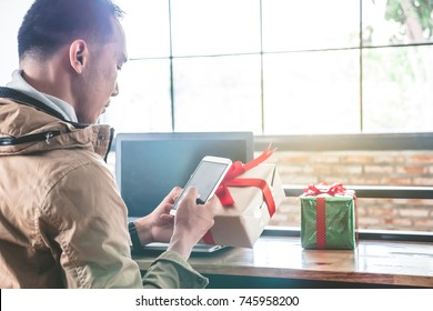 Happy man holding gift box and using smart phone in cafe. Asian man preparing presents for christmas holiday.