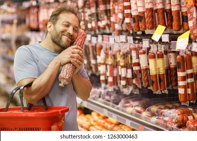 Happy man holding in hands near face salami and smiling. Bearded customer standing with closed eyes in meat section. Handsome man choosing delicious meat of whole assortment.