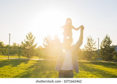 Happy man holding his little daughter on neck in summer park