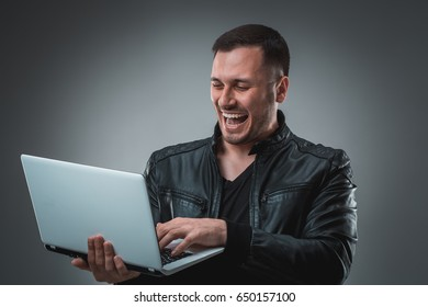 Happy man holding laptop on gray background