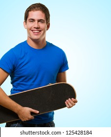 Happy Man Holding Skateboard against a blue background