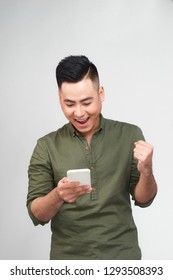 Happy man holding smartphone and celebrating his success over gray background