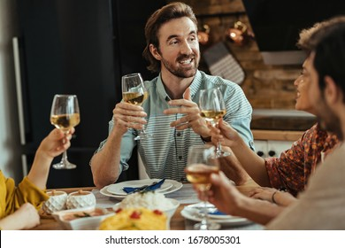 Happy man holding a toast and talking with his friends during a meal at dining table.