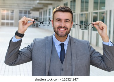 Happy man holding two pairs of glasses