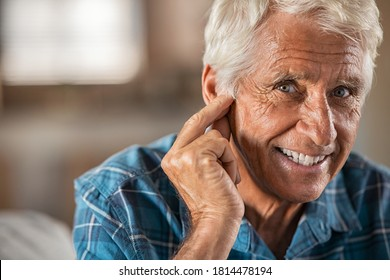 Happy man at home with hearing aid finally hears, copy space. Portrait of smiling senior man holding ear with satisfaction looking at camera. Close up face of old man at home with his new hearing aid.