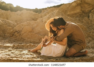 happy man hugging girlfriend in straw hat with floral bouquet in sand canyon