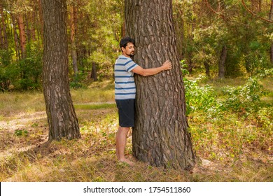A happy man hugging a tree in forest