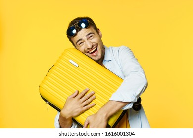Happy man hugs a suitcase and glasses on his head