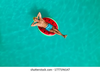 Happy man with inflatable ring in swimming pool, top view. Summer vacation