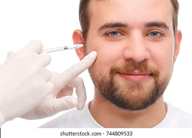 A happy man is injected botox into the face. Isolated over white background.