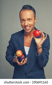 A happy man in a jacket holding apples