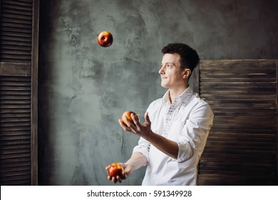 Happy man juggles apples standing in grey room