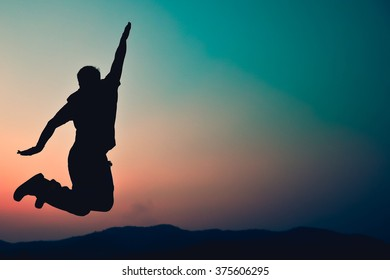 Happy man jumping against beautiful sunset