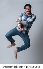 Happy man jumping full body kicking heels smiling dancing on air isolated against neutral background