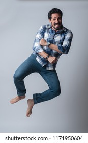 Happy man jumping full body kicking heels isolated against neutral background