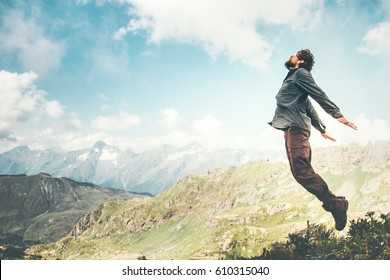 Happy Man jumping at mountains to clouds sky Lifestyle Travel emotional euphoria success concept adventure active vacations outdoor