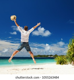 Happy man jumping on the tropical beach. White sand, blue cloudy sky and crystal sea of tropical beach. Vacation at Paradise. Happy island lifestyle. Ocean beach relax, travel to Maldives islands