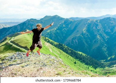 Happy man jumps up on a background of mountains