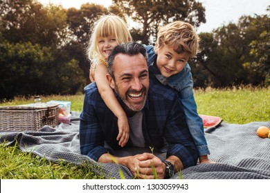Happy man with kids on a picnic lying down in park beside a picnic basket. Children lying on the back of their father.