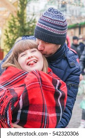 Happy man is kissing beautiful girl with the red cozy blanket