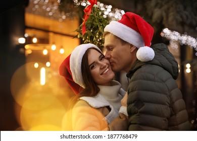 Happy man kissing his girlfriend under mistletoe bunch outdoors, bokeh effect