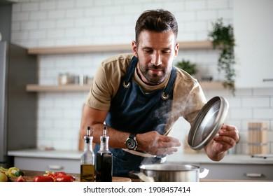 Fröhlicher Mann in der Küche. Junge Mann, der köstliches Essen zubereitet.