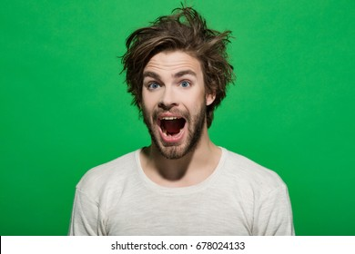 happy man with long stylish uncombed hair and smiling bearded man on green background, morning and barbershop fashion