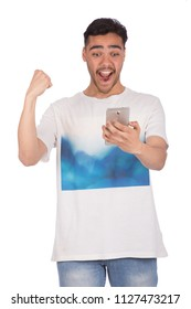 Happy man looking at his mobile phone and making victory sign, isolated on a white background.
