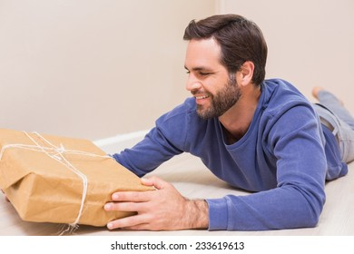 Happy man looking at package lying on the floor