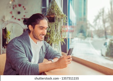 Happy man looking at phone smiling, texting. Closeup portrait of handsome guy wearing white shirt, gray blouse sitting near window at a table in living room. Mixed race, indian turkish caucasian model