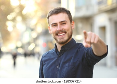 Happy man looks at you pointing at camera in the street
