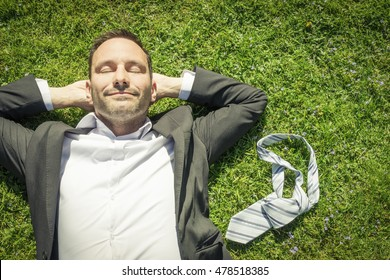 happy man lying in the grass relaxing and smiling