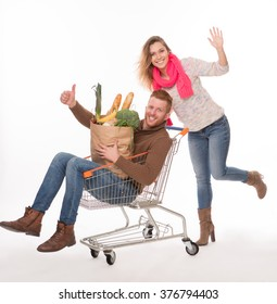 Happy man lying in shopping cart, holding bags with groceries and showing okey sign. Cheerful lady pushing shopping cart.