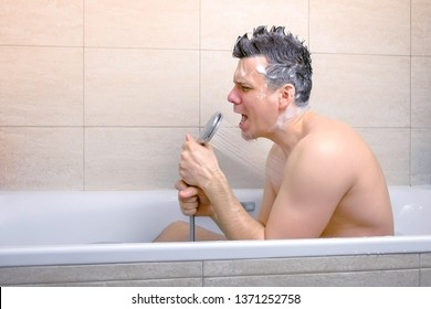 Happy man with Mohawk shampoo hairs is singing with shower as a microphone while he is washing in bathtub. And washing his head. Side view.