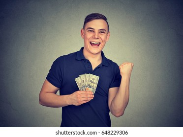 Happy man with money isolated on gray background
