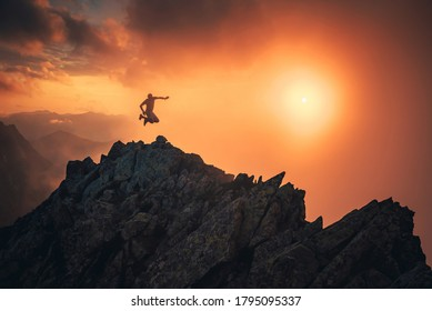 Happy man in mountains. Young hiker jumping on the top of the hill, sunset sky in background,