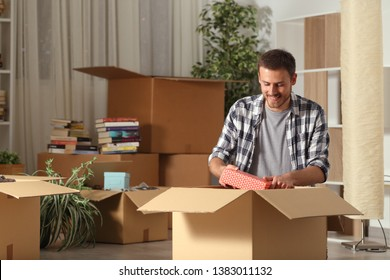 Happy man moving home unboxing belongings on the floor in the night